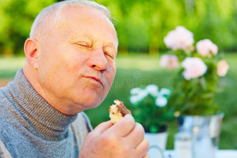Gamal man som äter kakan i trädgård royaltyfria foton