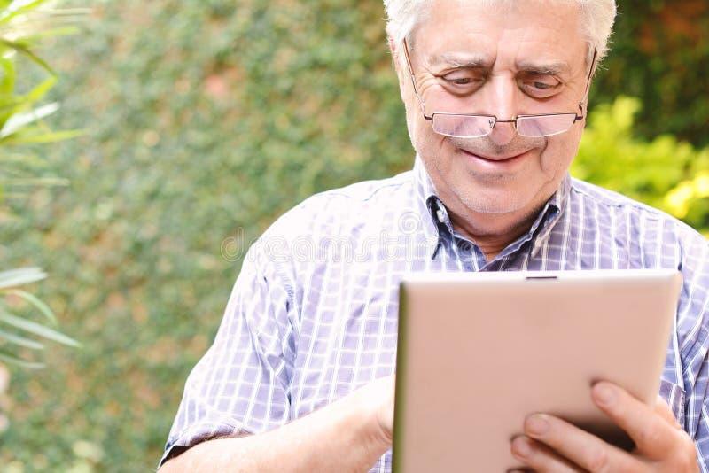 Gamal man som använder den digitala minnestavlan fotografering för bildbyråer