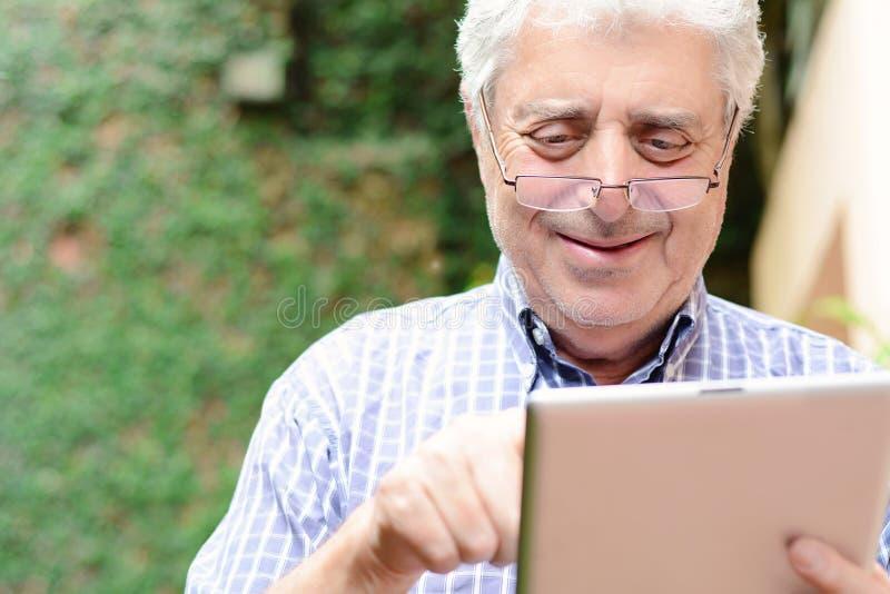 Gamal man som använder den digitala minnestavlan royaltyfri fotografi