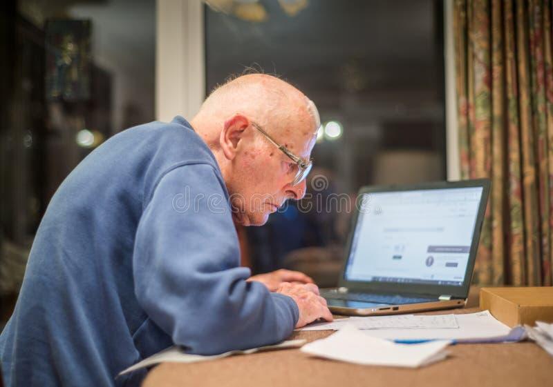 Gamal man som använder en dator, Hampshire, England, U K royaltyfria foton