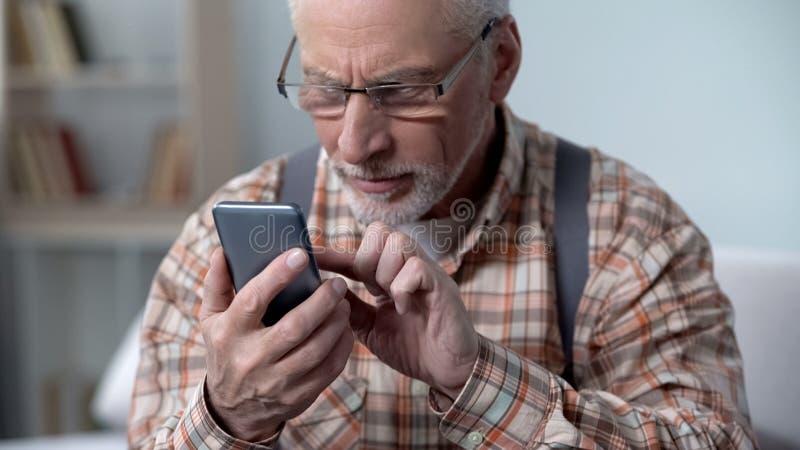 Gamal man som använder försiktigt smartphonen och att lära apps och nya tekniker, closeup royaltyfria bilder