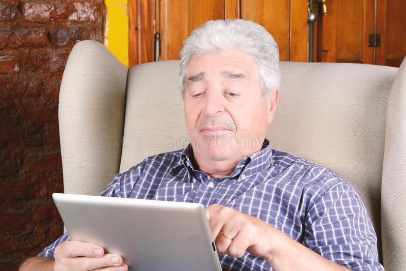 Gamal man som använder minnestavlan royaltyfria foton
