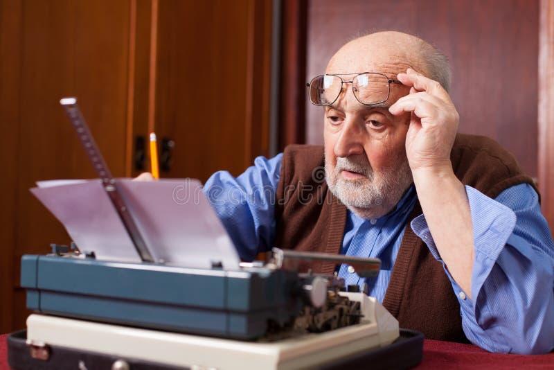 Gamal man som arbetar på en skrivmaskin arkivfoto