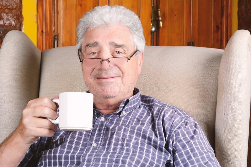 Gamal man som dricker kaffe arkivbild