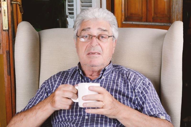 Gamal man som dricker kaffe fotografering för bildbyråer
