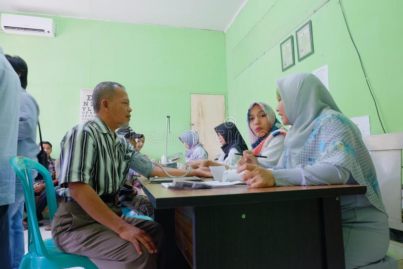 Gamal man som har den medicinska kontrollen upp för förnyandekörkort arkivbild
