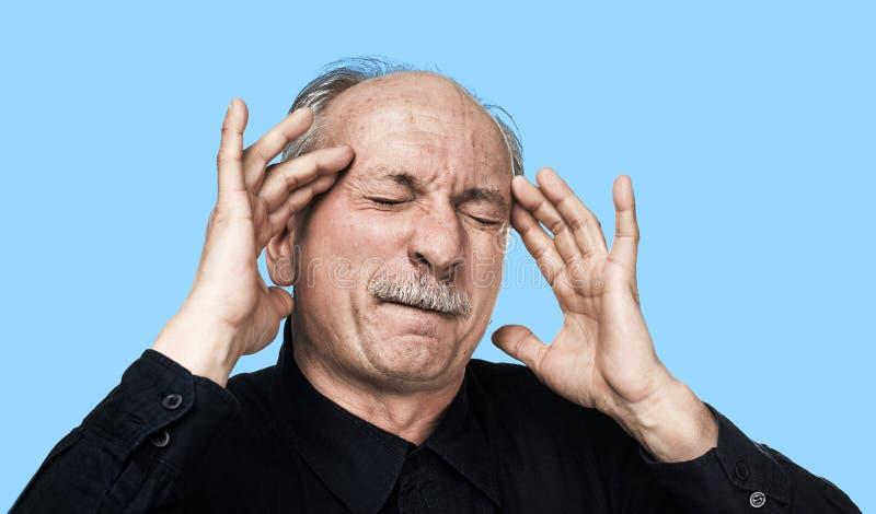 Gamal man som lider från en huvudvärk royaltyfria foton