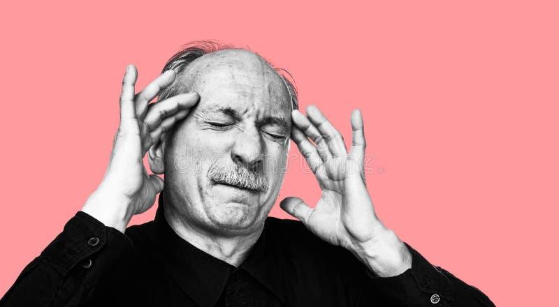 Gamal man som lider från en huvudvärk arkivbild