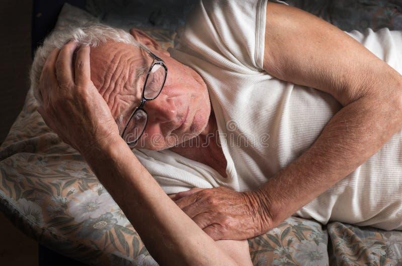 Gamal man som ligger i säng arkivfoton