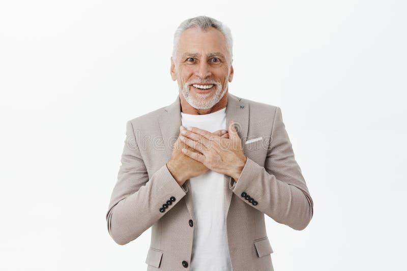 Gamal man som mottar nöjt och förtjust le för hjärtevärmande och rörande gåva med krokiga tänder på att rymma för kamera fotografering för bildbyråer