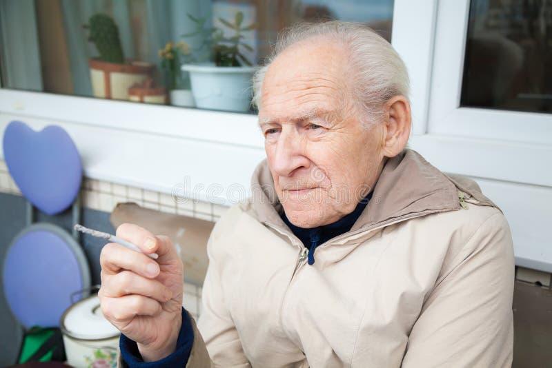 Gamal man som rymmer en cigarett arkivbild