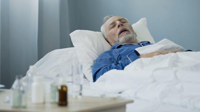 Gamal man som sover i säng på sjukhussalen, antibiotikummar som står på tabellen royaltyfria foton