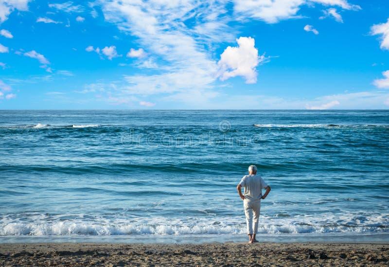 Gamal man som stirrar på havet royaltyfria bilder