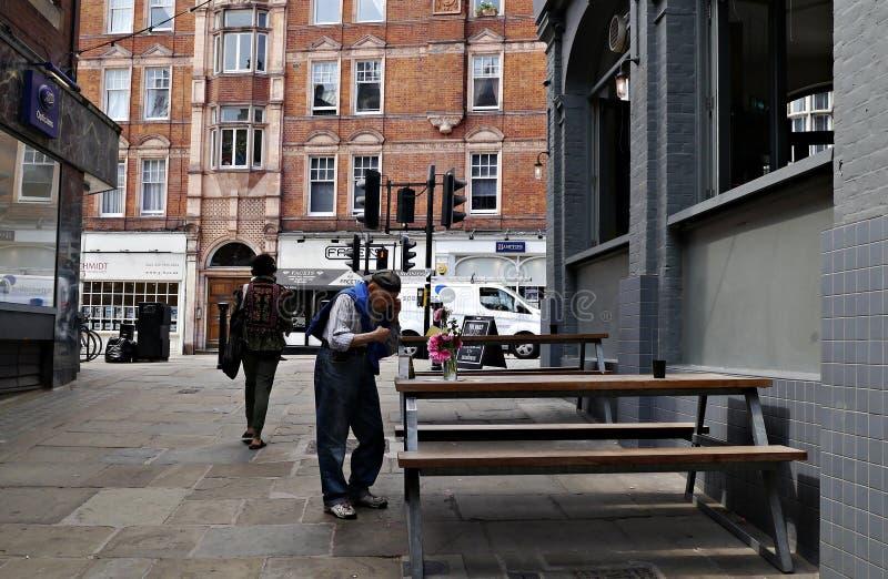 Gamal man som talar på hans mobiltelefon i Hampstead London UK arkivbild