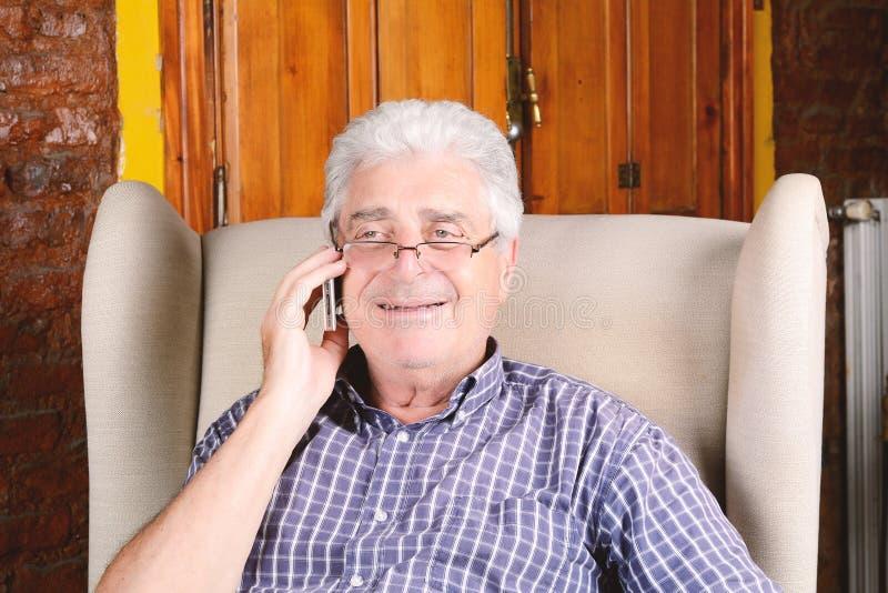 Gamal man som talar på telefonen royaltyfria bilder