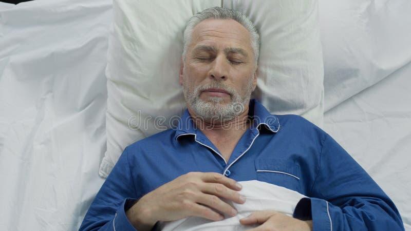 Gamal man som tycker om sova madrassen och kuddar för komfort tack vare den ortopediska arkivbild