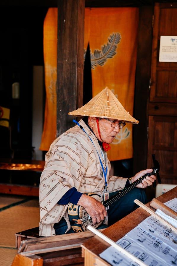 Gamal manhand som spelar Sanshin Okinawa - japanskt musikinstrument arkivfoton