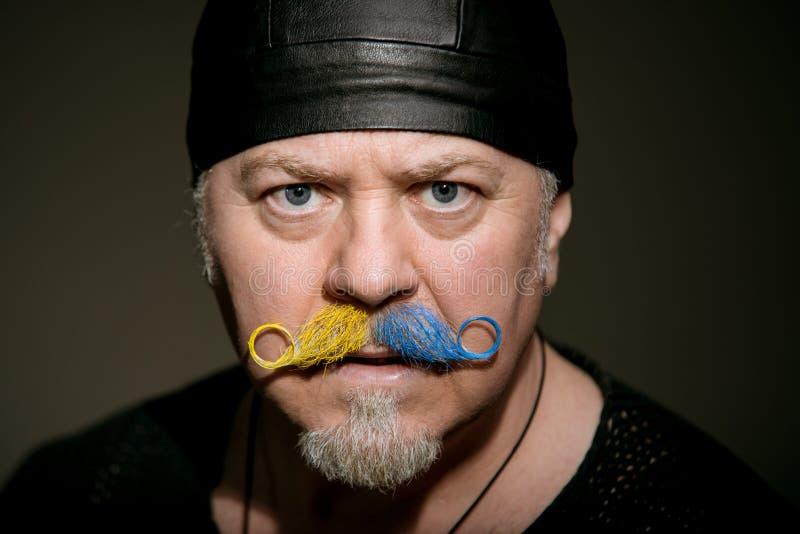 Gamal mankonstn?r med mustaschen i studion arkivfoton