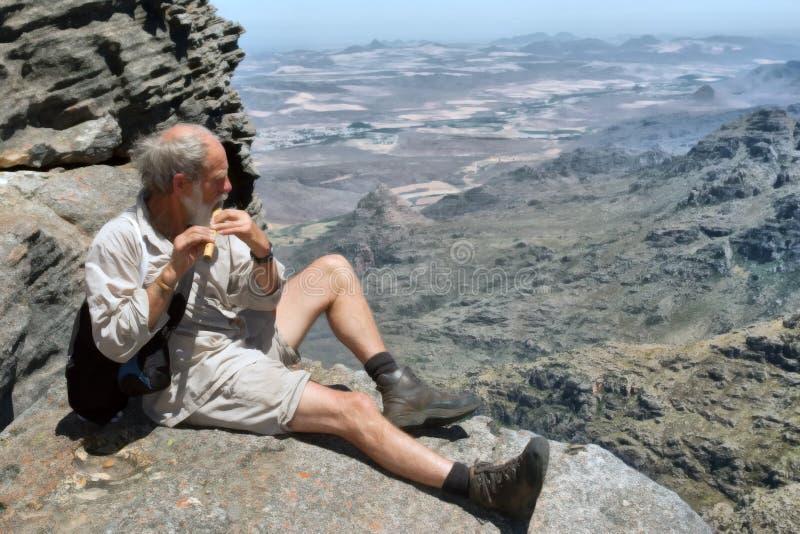 Gamal manlekar blåser flöjt överst av berg arkivbild