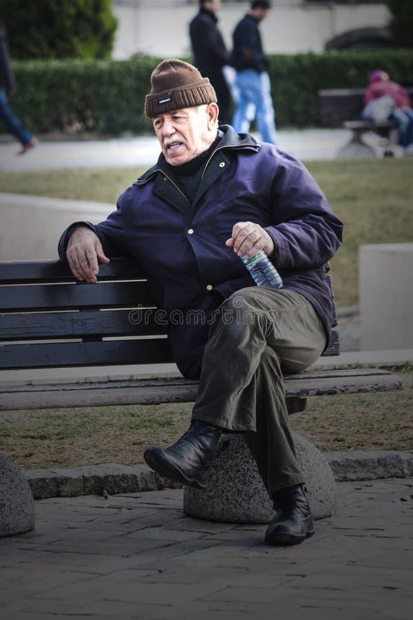 Gamal mansammanträde på en bänk royaltyfria foton
