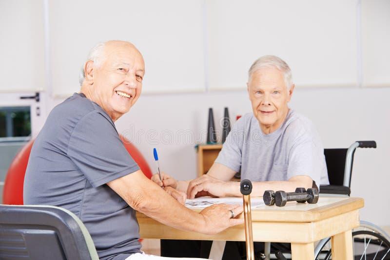Gamala män i vårdhemmet som löser korsordpusslet arkivbilder