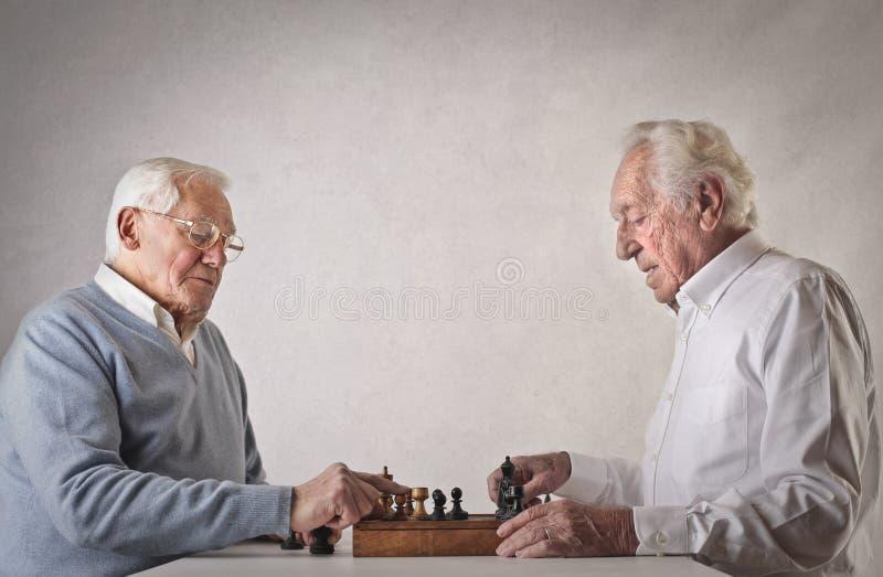 Gamala män som spelar schack royaltyfria foton