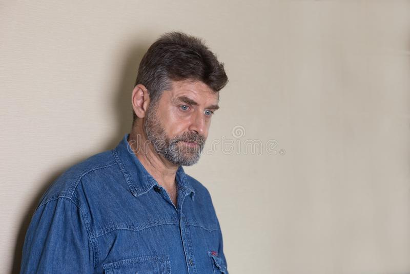 Gamala mannen är ledsen i väggbakgrund arkivbilder