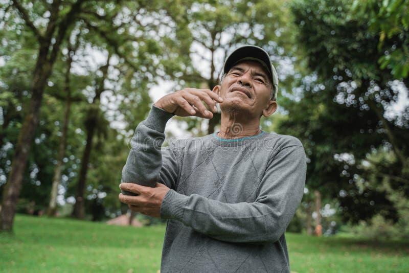 Gamala mannen att rymma hans armbåge med allvarligt smärtar royaltyfri bild