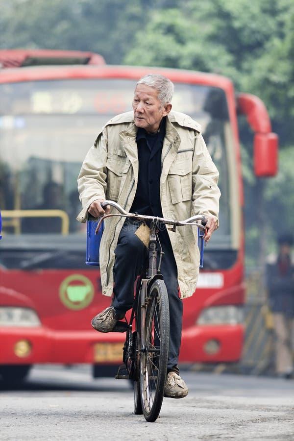 Gamala mannen cyklar i ottan med bussen på bakgrund, Guangzhou, Kina arkivfoto