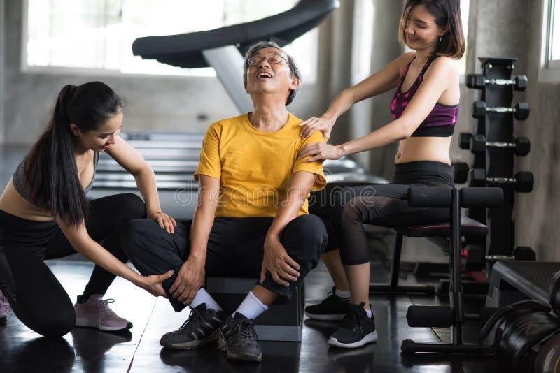 Gamala mannen får massage av kvinnor på konditionidrottshallen arkivbild