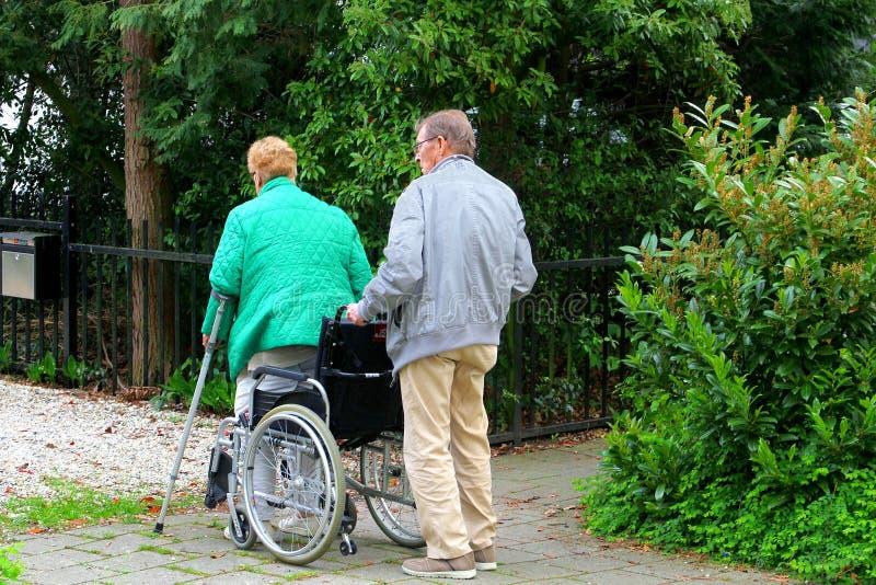 Gamala mannen hjälper hans fru i en rullstol, Nederländerna royaltyfri foto
