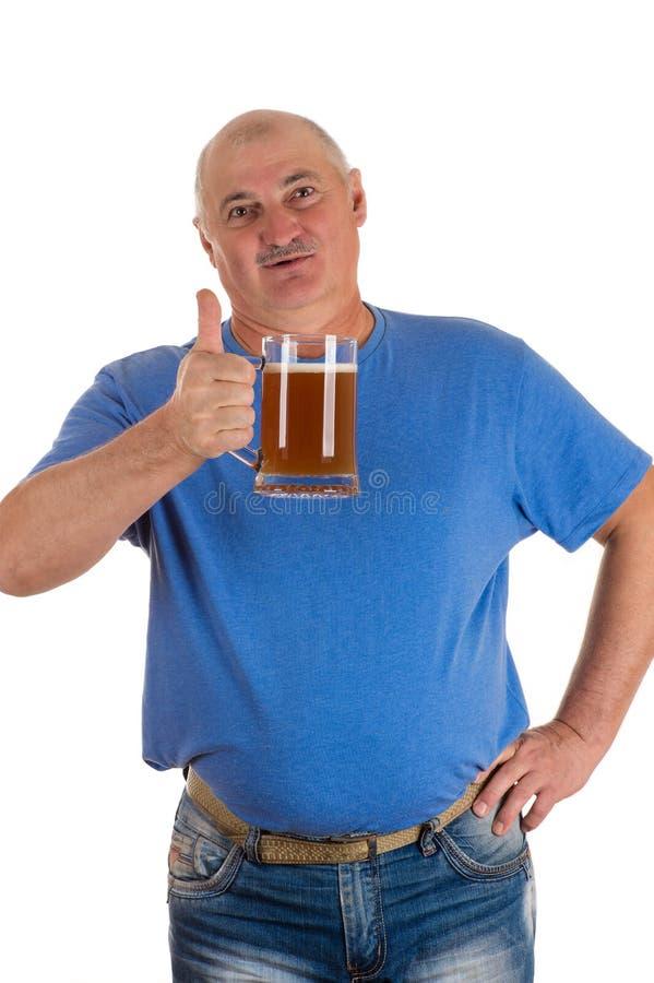 Gamala mannen med ett öl i handvisning tummar upp arkivfoton