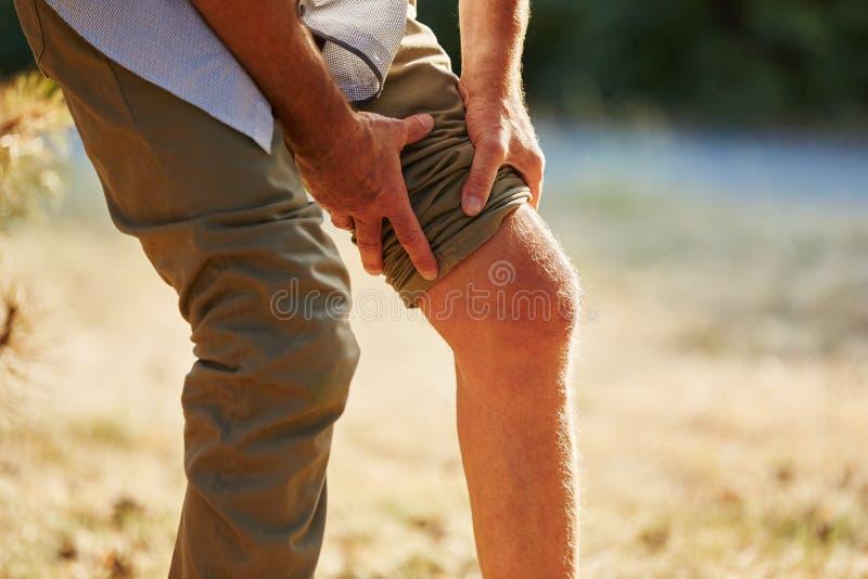 Gamala mannen med smärtar på knäet fotografering för bildbyråer