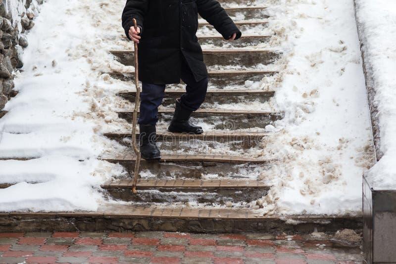 Gamala mannen ner trappan som är hal i vinter arkivbilder