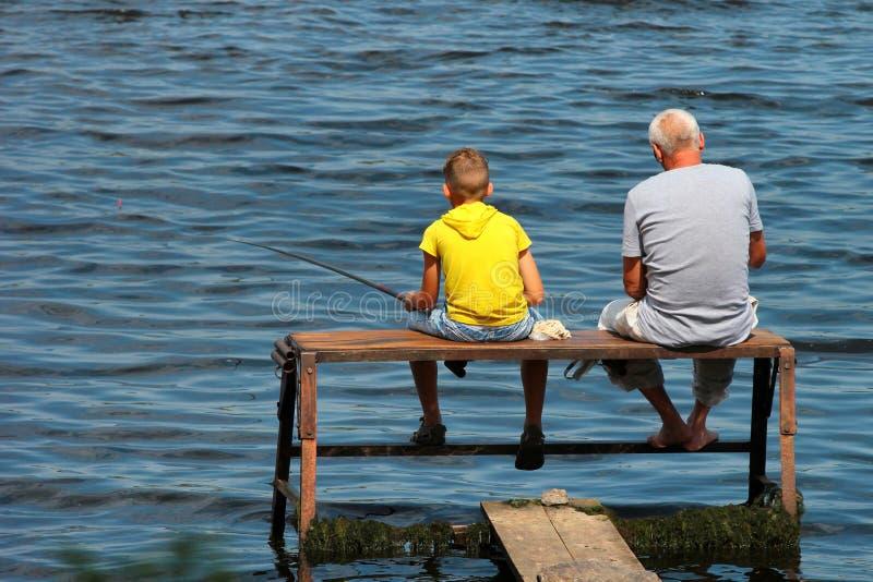Gamala mannen och en pojke sitter på engjord fiska plattform med stänger arkivfoto