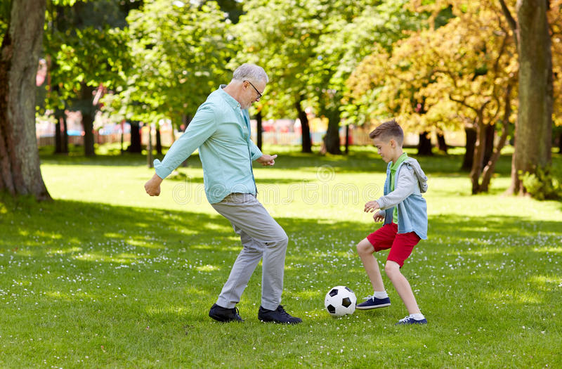 Gamala mannen och pojken som spelar fotboll på sommar, parkerar fotografering för bildbyråer