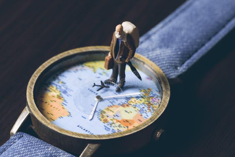Gamala mannen på klockor med världskartan, tappning tonade fotoet Världsloppbaner Hög handelsresandestatyett arkivfoto
