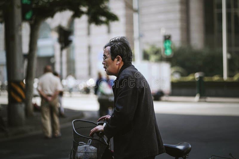 Gamala mannen rymmer hans cykel som korsar vägen fotografering för bildbyråer