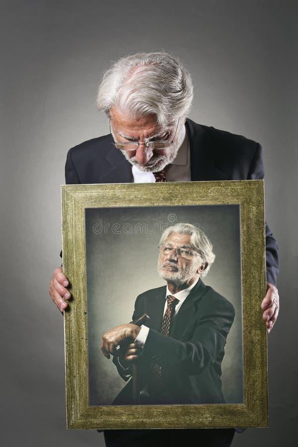 Gamala mannen ser en målarfärg av honom royaltyfri fotografi