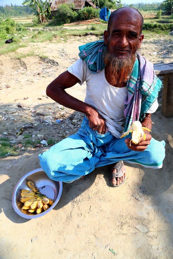 Gamala mannen sitter med bananen royaltyfri foto