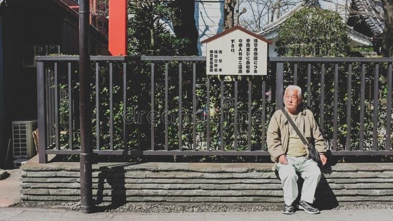Gamala mannen sitter på bänken Asakusa Japan royaltyfri foto