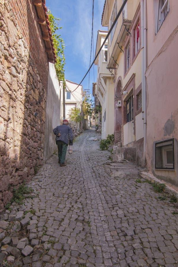 Gamala mannen som går ner gatorna av Ayvalik arkivbilder