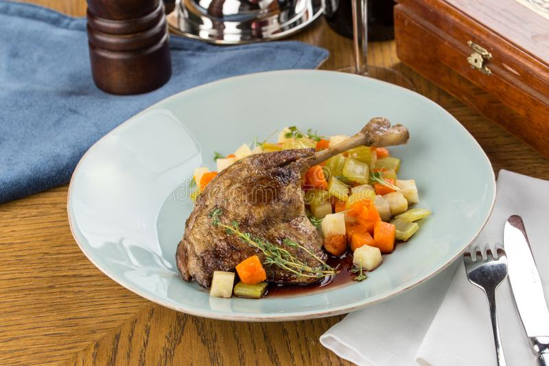 Gamba dell'anatra arrostita con lo stufato di verdure in piatto blu sul menu di legno del ristorante della tavola fotografia stock