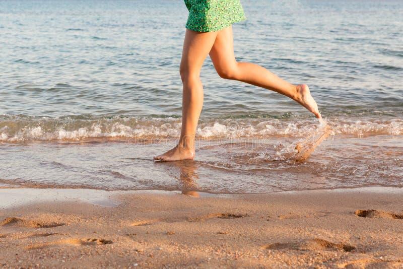 Gamba della donna che corre sulla spiaggia con la spruzzatura dell'acqua Vacanza di estate gambe di una ragazza che cammina in ac fotografia stock
