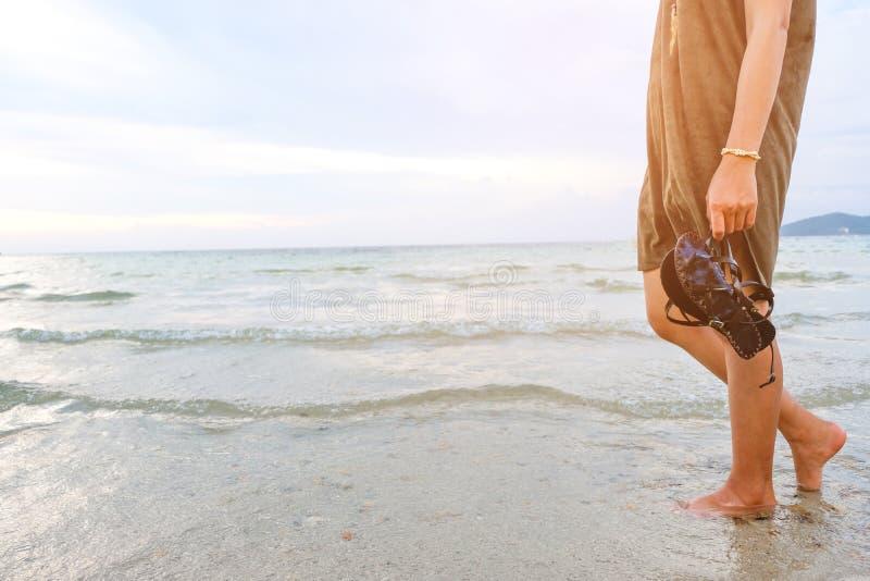 Gamba della giovane donna che cammina lungo l'onda dell'acqua e della sabbia di mare sulla spiaggia in isola tropicale con l'atte fotografie stock