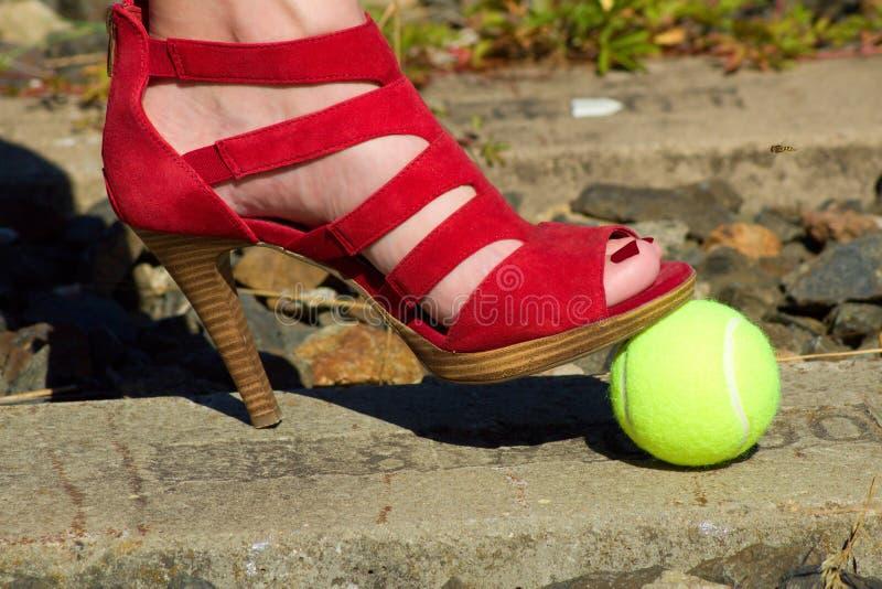 Gamba delle signore - piede nella scarpa della corte ed in una pallina da tennis fotografia stock libera da diritti