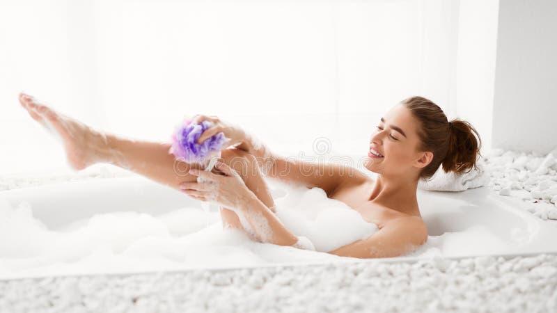 Gamba di lavaggio della donna con la spugna nel bagno con schiuma immagini stock