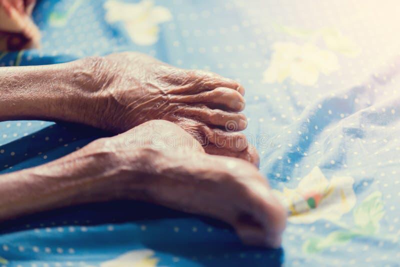 Gamba di sonno della donna anziana a letto immagine stock