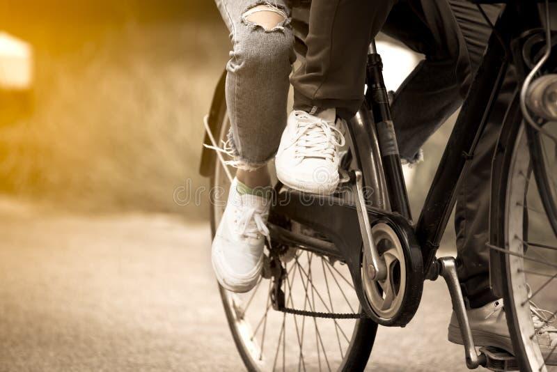 Gamba e piedi di giovani coppie che guidano insieme una bicicletta fotografia stock