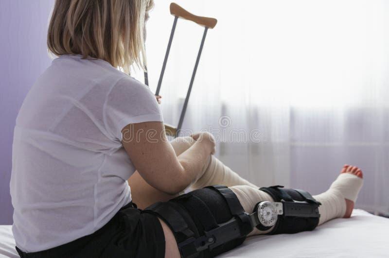 Gamba femminile dopo la chirurgia del ginocchio in fasciature e nell'ortesi fotografia stock